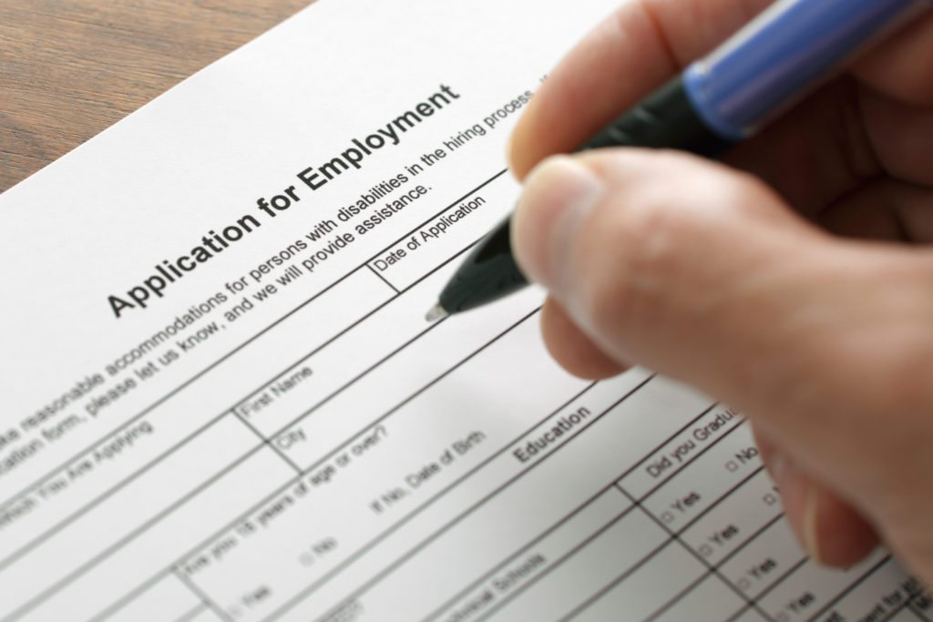 Completing an employment application form with focus on heading